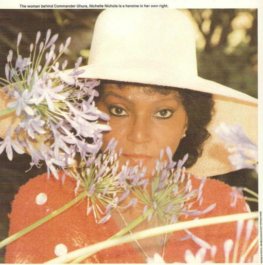 Nichelle Nichols in 1987 in a straw hat posing behind purple flowers