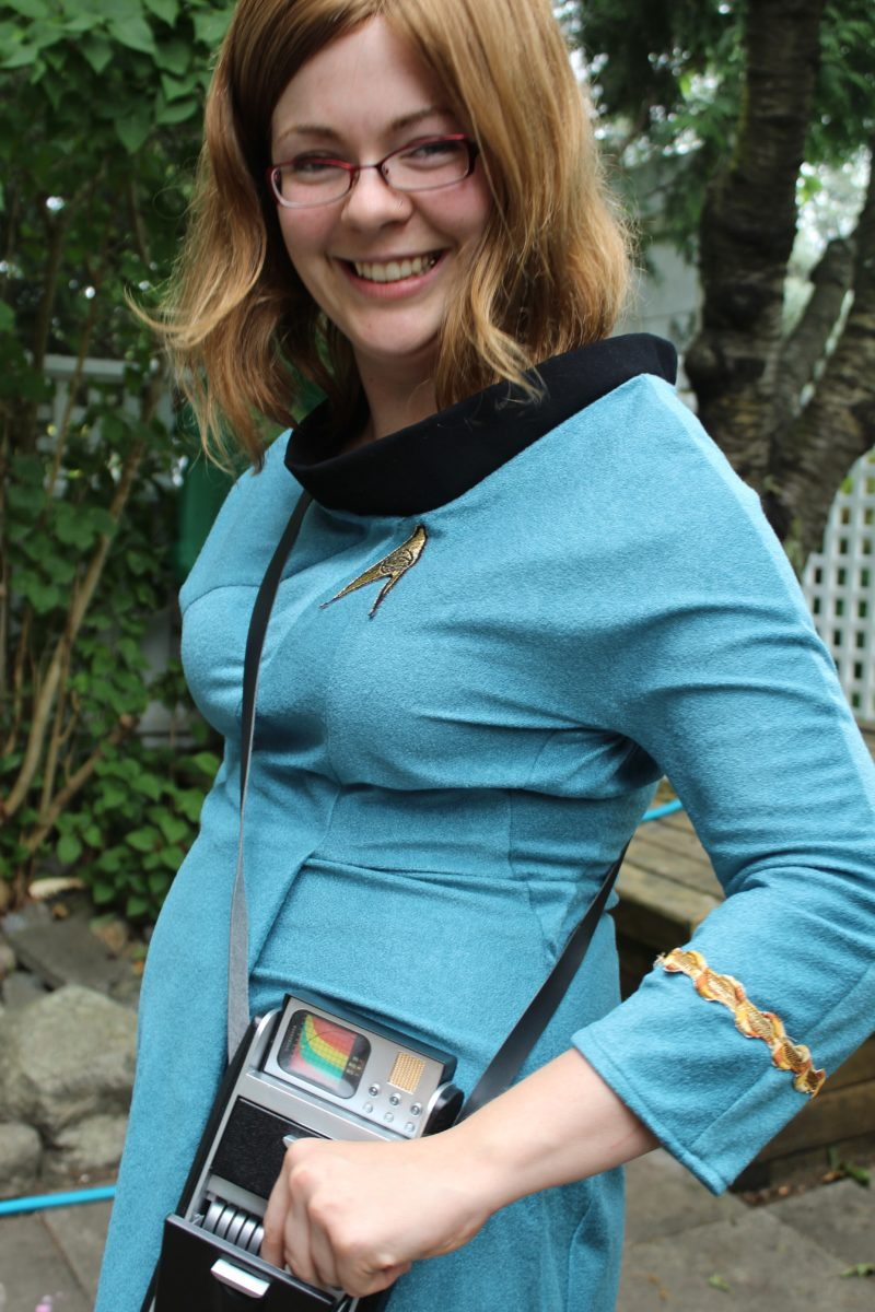 Jarrah in a TOS blue science uniform with tricorder