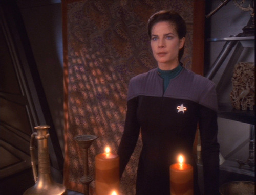 Jadzia stands in her uniform in her quarters behind two large candles
