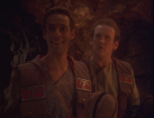 Bashir and O'Brien in brown outfits with Klingon symbols, in the cave where the bachelor party is held