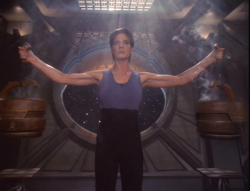Jadzia holds two steaming, heavy braziers aloft, one in each hand