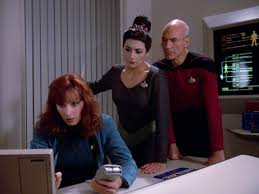 Troi and Picard look over Crusher's shoulder