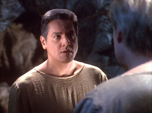 Chakotay in a brown robe talking to the alien