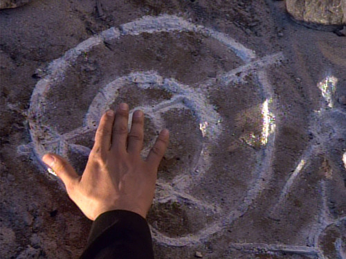 Chakotay's hand touching strange symbol