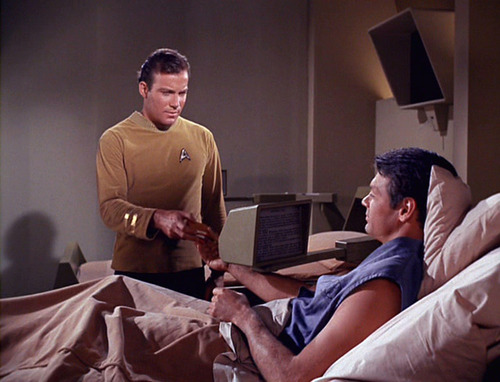 Mitchell reads a book on a computer screen in sickbay