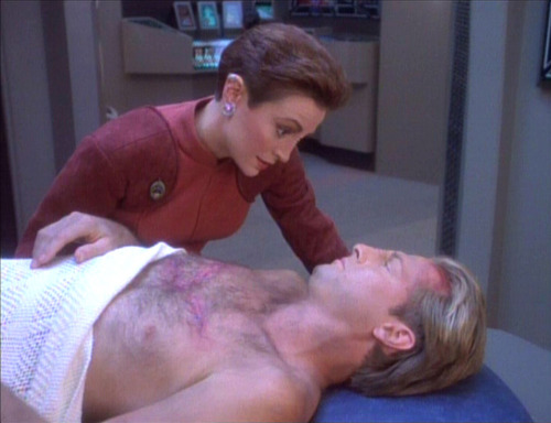 Kira leans over Tahna in his infirmary bed