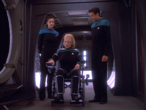 Dax and Bashir walk with Melora in her wheelchair