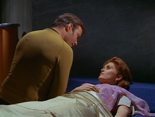 Kirk leans over Janice in bed