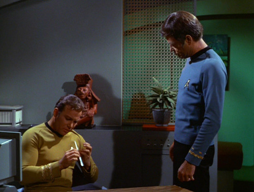 Kirk files his nails while Spock watches