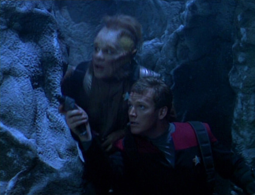 Neelix and Paris hide behind a rock