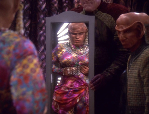 Quark examines his new body in the mirror