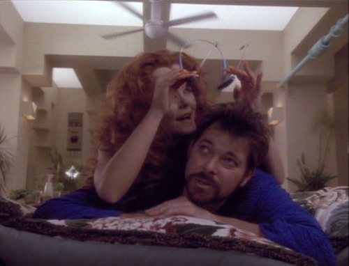 Etana puts a game headset on Riker