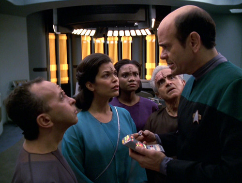 Group of Qomar stare at The Doctor in Sickbay