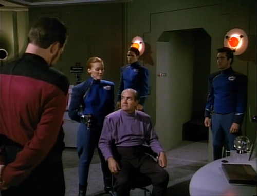 Davos interrogates a man while Riker watches