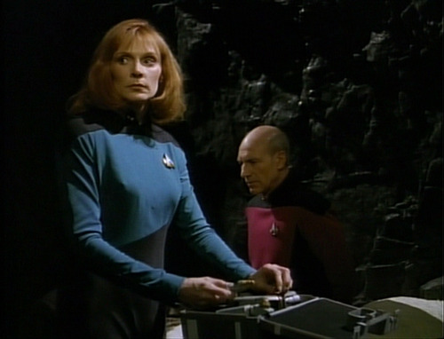 Crusher looks out for anyone coming while she talks to Picard