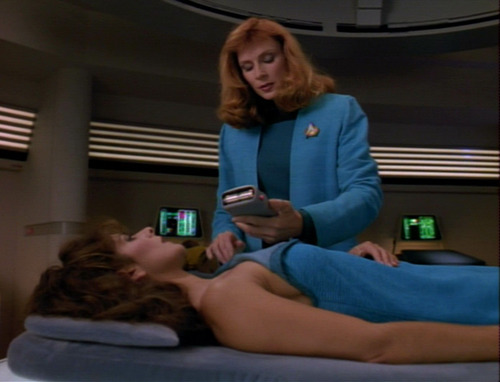 Crusher scans Troi in Sickbay, who is lying naked under a blue blanket
