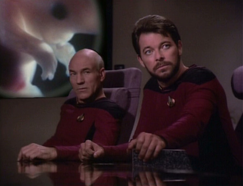 Riker and Picard sit at conference table in front of image of Troi's fetus