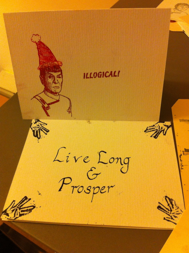 "Card with stamp of Spock in a Santa hat saying ""illogical"" and another card with stamped Vulcan hands and ""Live Long & Prosper"""
