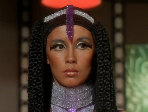 Elaan's face, with Cleopatra-esque hair, Egyptian-inspired eye makeup, and a purple tiara