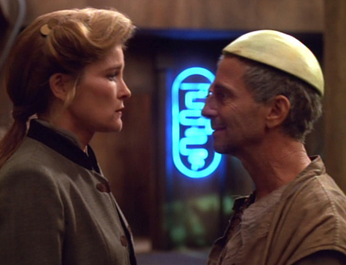 Janeway and Caylem, who is wearing a half-melon on his head
