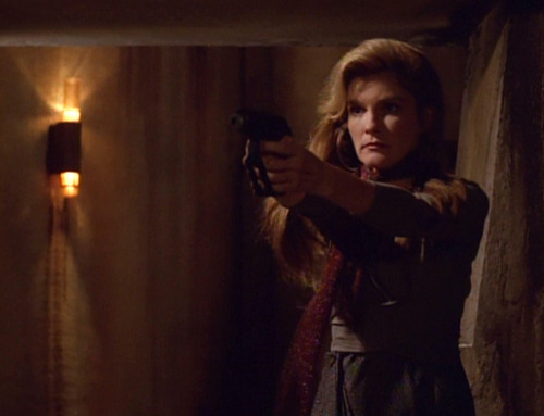 Janeway holds a weapon out to threaten the prison guards