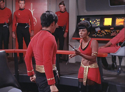Uhura holds a dagger pointed at Mirror Sulu