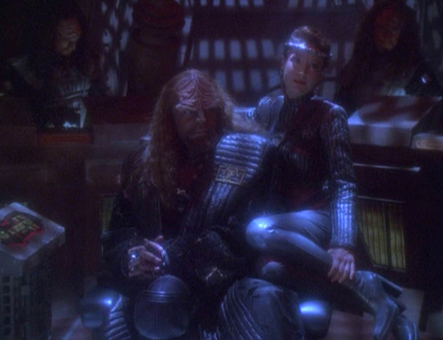 Intendant Kira sitting on Emperor Worf's lap