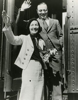 Celia Lovsky and Peer Lorre wave from the steps of a train