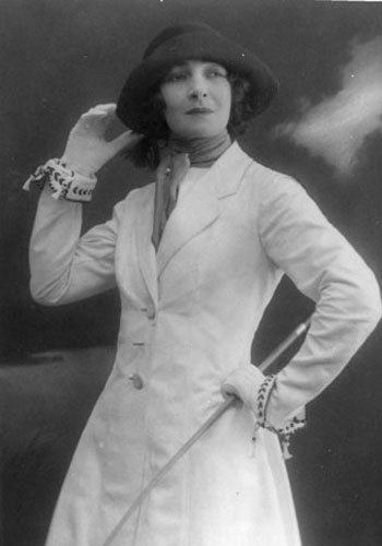 A young Celia Lovsky poses for the camera in a white dress, dark hat and gloves