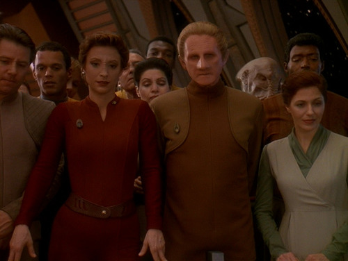 Kira and Odo stand in a crowd on the Observation Deck