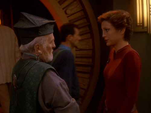 Kira talks to an older male Vedek outside the temple on DS9