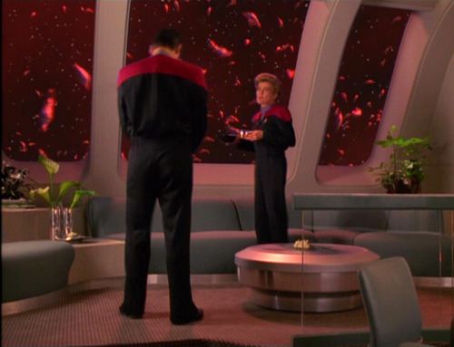 Janeway and Chakotay talk in her ready room, with spawning aliens outside