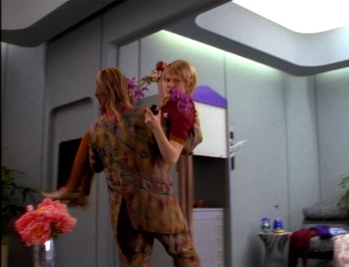 Neelix carries Kes out of her quarters, her clutching flowers