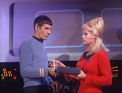 Rand gives Spock a padd to sign