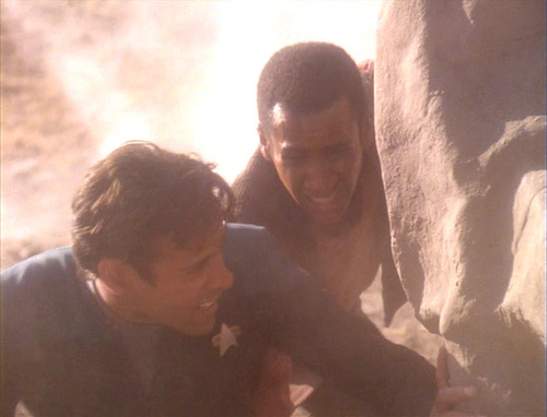 Jake and Bashir hide behind a rock