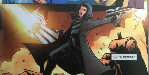 A white female Khan, in a hooded coat and all black, fires large, menacing weapons.