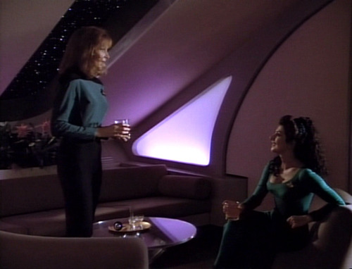 In her quarters, Crusher stands and talks to Troi, seated