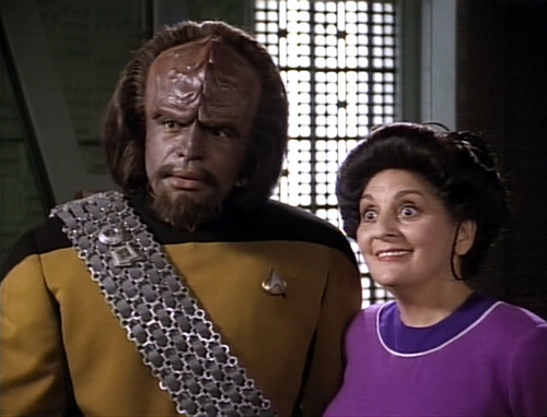 Worf stands beside an excited Helena in the transporter room