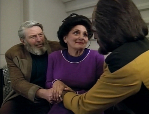 Worf's parents clasp his hands in a gesture of comfort and support, as they sit in his quarters