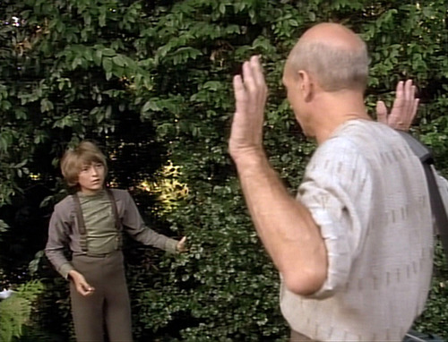 Picard puts his hands up as Rene comes out of the bushes and surprises him