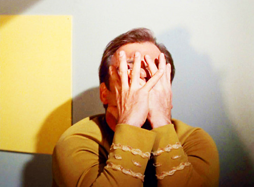 Kirk covers his face with his hands, as if in pain