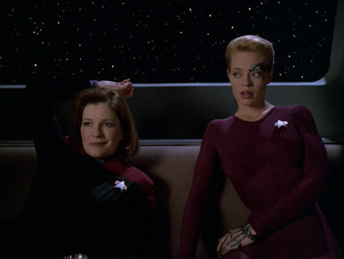 Janeway sits on a sofa next to Seven