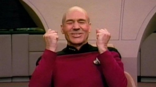"Picard smiling and holding his fists up as if to say, ""Yes!"""