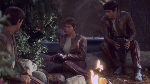 T'Mir and her Vulcan crewmates sit around a fire in the woods