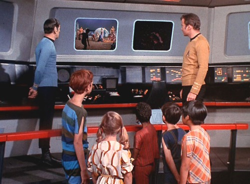 The kids, Kirk and Spock watch the video of their families from the bridge