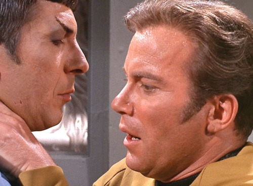 Kirk leans on Spock for support, their faces close