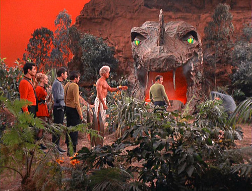 Kirk and his crew stand by the mouth of the cave
