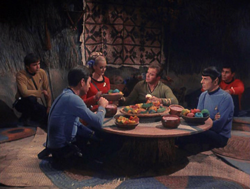 away team sits around a low table in a hut, eating and talking
