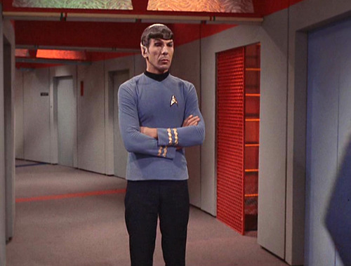 Spock in the Enterprise corridor, arms crossed, looking skeptical