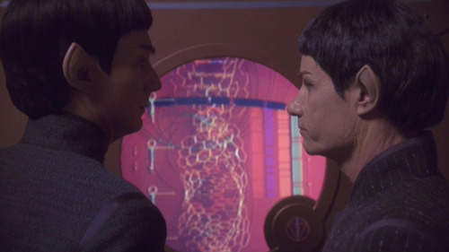 2 male Vulcans look at each other meaningfully after viewing a medical scan